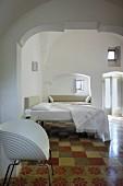 White designer chair on tiled floor in restored bedroom of historical building