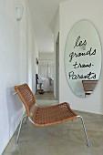 Loungestuhl vor ovalem Wandspiegel mit Spruch und Blick in Schlafbereich