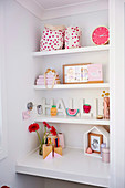 White built-in shelves with girl accessories above built-in desk