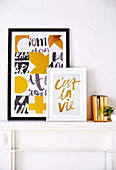 Framed prints on white mantelpiece