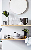 Shelf with dishes and flower vase under a round wall mirror