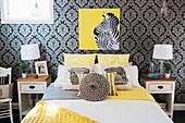Schlafzimmer mit dunkel gemusterter Tapete und gelben Akzenten
