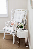 White painted rattan chair and side table with bouquet and necklace from Bali in the corner of the room