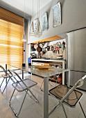 Essbereich vor einfacher Küchenzeile mit aufgehängten Kupferpfannen