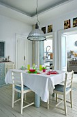 Set table and colourful glass crockery on white wooden floor in dining area