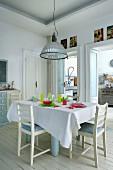 Weisser Dielenboden in Essbereich mit gedecktem Tisch und buntem Glasgeschirr