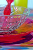 Red fork on glass bowl on colourful place mat