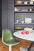 Green, retro shell chair in front of grey fitted cupboards and shelves