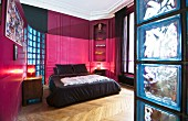 Hot-pink panelled walls and stucco ceiling in bedroom of period apartment