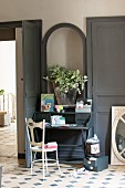 Dark grey writing desk below picture frame