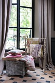 Various fabrics on valet stand and cushions on wicker trunk in front of lattice window