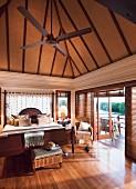 Doppelbett und Korbmöbel in elegantem, hohem Schlafzimmer mit Balkon