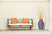 Rustic carved wooden bench with seat cushion, bolsters and scatter cushions next to branches arranged in floor vase