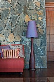 Sofa and standard lamp against stone-clad wall