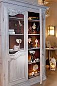 Antiker Holzschrank mit verschiedenen Dekoobjekten in nostalgischem Ambiente