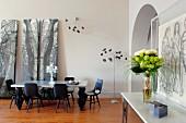 Esszimmer mit hohen Decken, Bogentür und Waldbildern