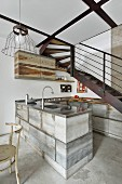 Rustic, industrial-style kitchen below metal staircase