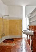 Badezimmer mit alten Fliesen und vertikalem Lichtschacht