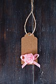 Brown paper tag with pink fabric rose and ribbon
