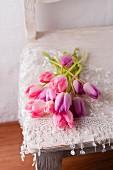 Tulpen in Rosa und Lila liegen mit einem Spitzentuch auf einem Stuhl
