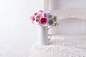 Primulas in jug on lace doily on chair