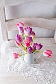 Pink and purple tulips in jug on lace doily on white chair