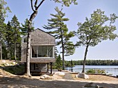 Modern, architect-designed house on stilts next to lake