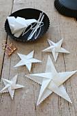Aus weißem Papier gefaltete Sterne mit Zackenrand