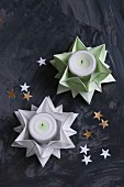 Folded green and white paper stars used as tealight holders