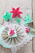 Folded paper flowers on lace and fabric rosette