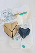Origami hearts and washi tape on printed paper