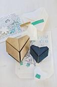 Origamiherzen mit Masking Tape auf Buchseiten und Papier