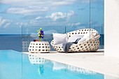 White outdoor furniture next to pool with view of sea and clouds in blue sky