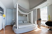 Four-poster bed in sophisticated bedroom in shades of grey