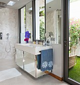 Mirrored washstand and doorway leading outside in bathroom