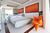 Schlafzimmer mit verspiegelter Wand und orangenen Akzenten