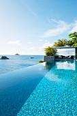 Luxurious infinity pool next to sea below blue sky