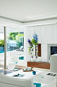 White modern living room with panoramic window leading to terrace