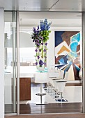 Vertical flower arrangement on tall table next to modern bar stools
