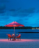 Romantic twilight atmosphere with armchairs below illuminated parasol on sandy beach