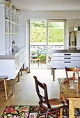 Rustic wooden table and white dresser with open shelves in the kitchen and view through open doors onto balcony