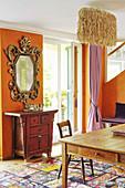 Brockspiegel und chinesischer Kommode vor orangefarbener Wand, Lampe aus Kokosfasern über Esstisch