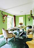 Massivholz-Tisch, Vintage Bänke mit Rentierfellen und Sessel mit Samtbezug in grünem Esszimmer mit Büffelschädel an der Wand