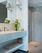 Mosaic tiles, open shower area and fresh flowers in bathroom