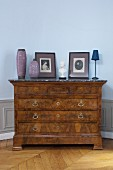 Antique burl chest of drawers with marble top against blue wall