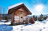 Kleine Holzhütte in verschneiter Winterlandschaft