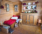 Small bed in festively decorated wooden cabin