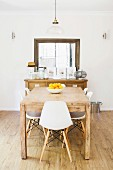 Rustic wooden table with white shell chairs, console table and rammed wall mirror in the background