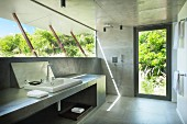 Concrete bathroom with glass wall and view into green garden