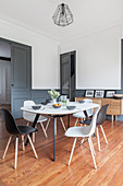 Dining table and chairs in interior with white walls and dove grey wainscoting